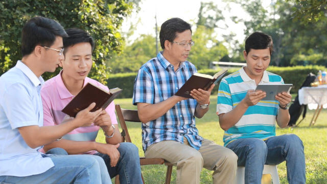 Quatro cristãos leem as palavras de Deus na grama