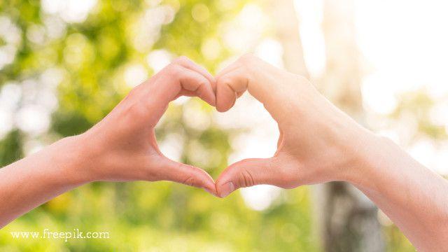 Casal segurando mãos coração