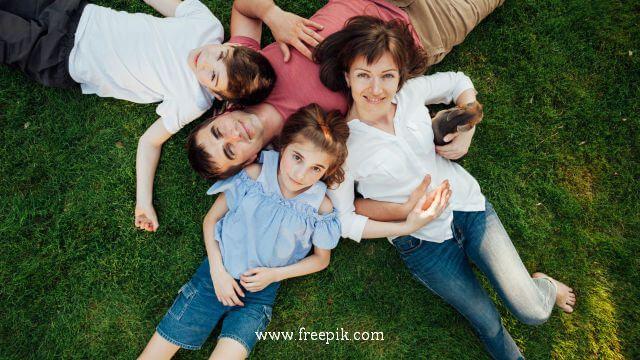 Uma família de quatro pessoas alegremente deitado na grama
