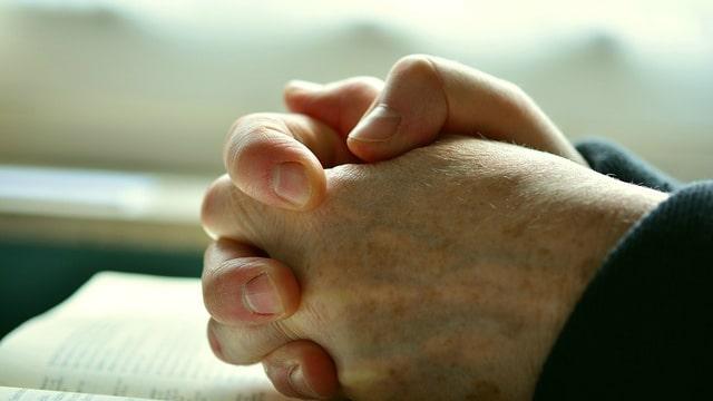 Uma mulher idosa ora a Deus